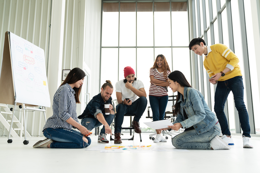 Young creative diverse group meeting and looking at project plan lay out on floor discuss or brainstorm business strategy with post note. Workshop for startup team in modern office. Happy workplace. (Young creative diverse group meeting and looking at